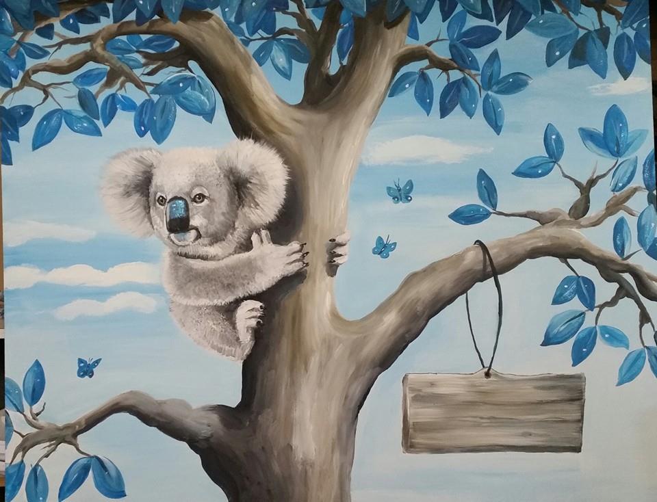 Koala in boom met naambordje