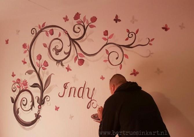 De naam Indy met sierdingen/bloemen en vlinders er omheen