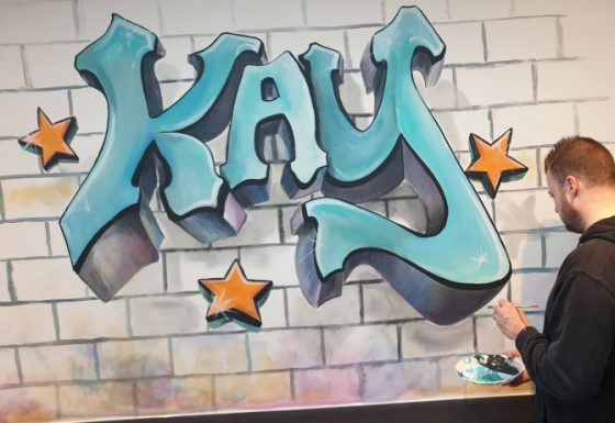 Kay in grafitti-letters in speelruimte